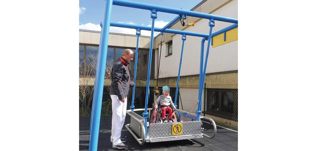 kleine Patientin auf Rollstuhlschaukel